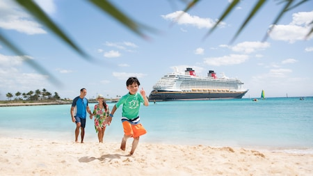 A mother, father and their young son walking on a sandy beach near a Disney cruise ship