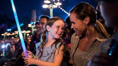 ライトセーバーを持って母親に向かって微笑む少女