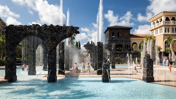 Several children playing in the poolside splash zone at Four Seasons Resort Orlando