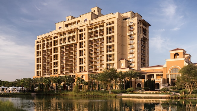 Exterior day view of magnificent Four Seasons Resort Orlando, framed by palm trees and a lake