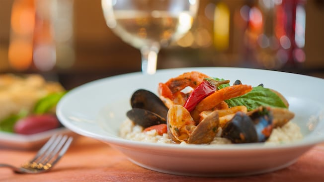 Elegant dinner setting includes a glass of white wine and a colorful array of clams on risotto