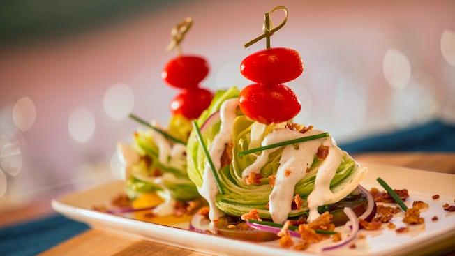 Two wedges of lettuce drizzled with bacon bits, creamy dressing and onions, topped off with cherry tomatoes
