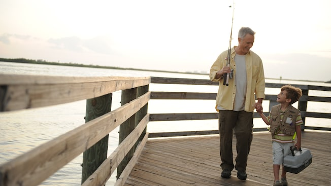 On a pier, a grandfather with a fishing pole holds the hand of his grandson, who holds a tackle box