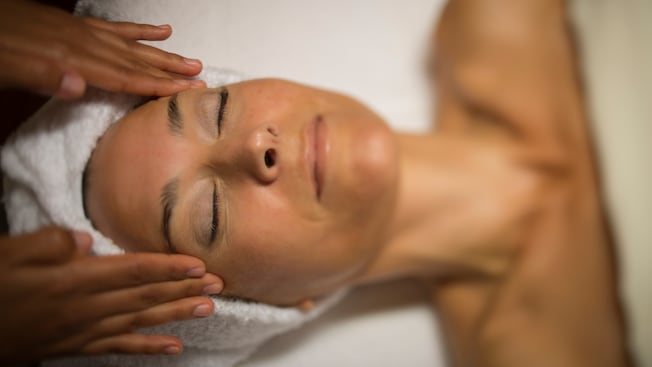 Close-up of a blissful woman on a spa table having her temples massaged