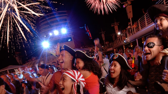 A audience dressed as Pirates of the Caribbean characters marvel at the fireworks going off overhead