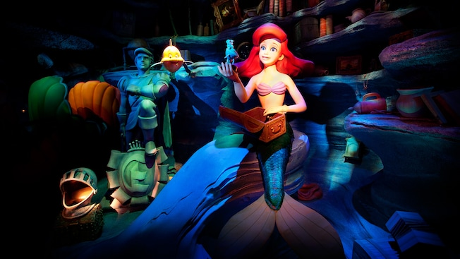 An Audio-Animatronics figure of Ariel looks through a small treasure chest