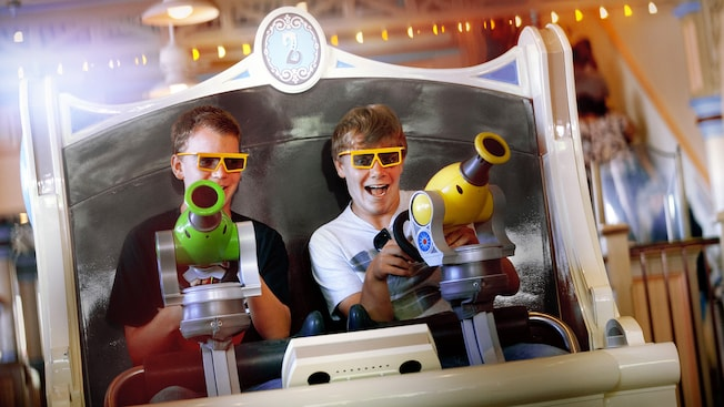 Two teen boys use their spring-action shooter on the Toy Story Mania! attraction