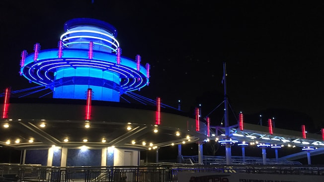 The Autopia Disneyland Park attraction, lit up at night, with a sign that says Powering Your Dreams Through Tomorrow