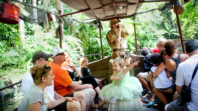 A young princess points to something exciting while the skipper shares stories with Guests aboard a Jungle Cruise boat.