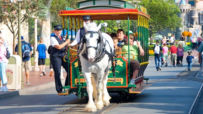 A horse pulls an open streetcar full of Guests down Main Street U.S.A.
