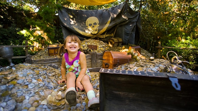 A pig-tailed girl sits on a pile of coins at Pirate's Lair on Tom Sawyer Island