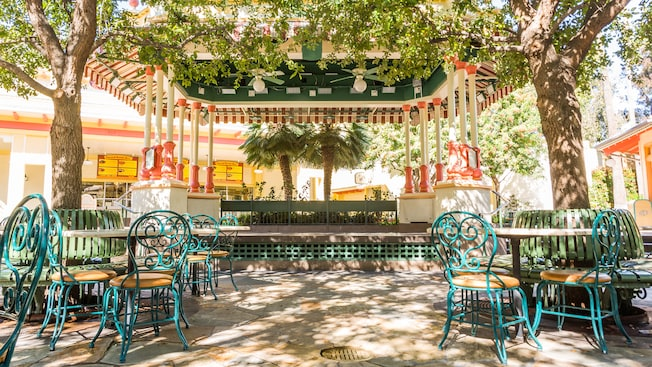 Paradise Garden Bandstand is surrounded by shady trees, with tables and chairs near the stage
