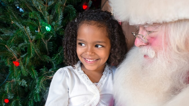 A little girl smiles as she visits with Santa Claus
