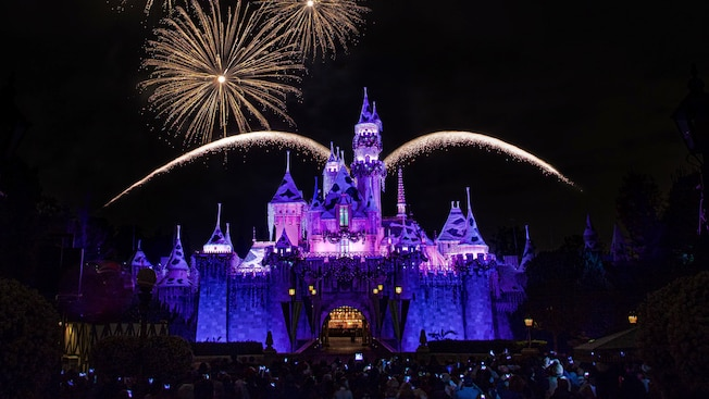 Fireworks burst over Sleeping Beauty Castle at Disneyland Park during the Believe in Holiday Magic nighttime spectacular