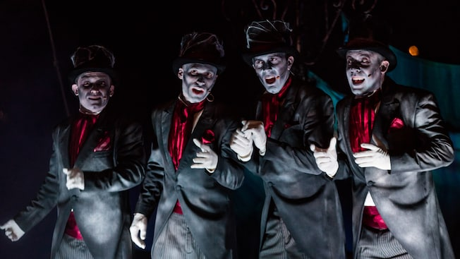 Members of the Cadaver Dans perform on a graveyard-themed raft on the Rivers of America at night