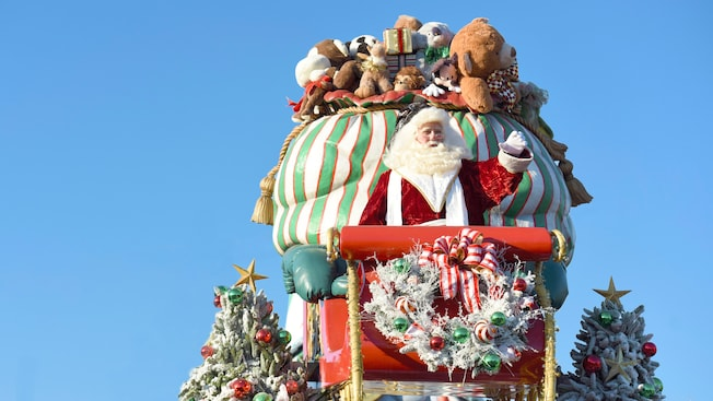 Santa Claus waves from the front of his sleigh, which is loaded with toys.