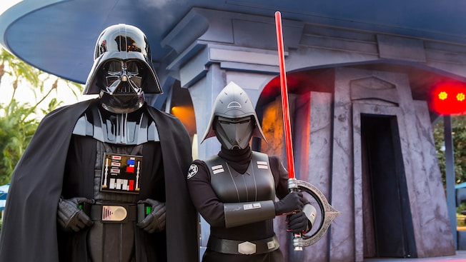 The Seventh Sister Inquisitor stands with lightsaber drawn, next to Darth Vader in front of a temple
