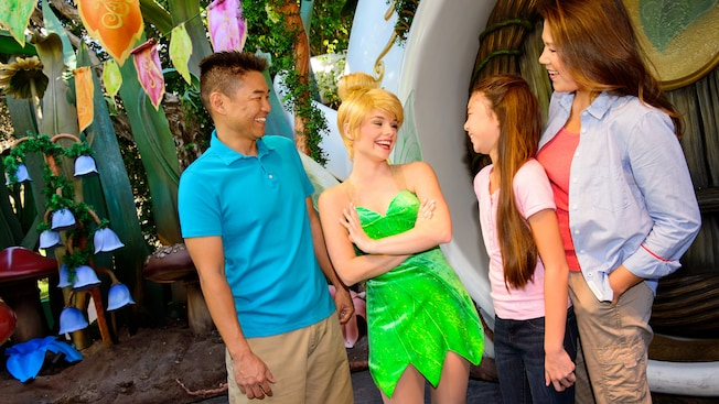 Tinker Bell greets a family in front of her woodland home in Pixie Hollow