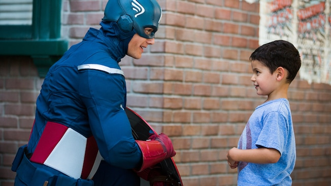 Captain America holds his shield to the side as he kneels to greet a young boy