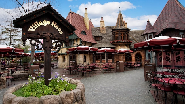 Entrance sign and outdoor dining courtyard at Village Haus Restaurant in Disneyland Park