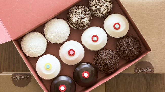 One dozen cupcakes with a variety of decorations and toppings in an open cardboard box