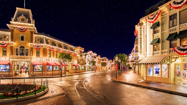 Stars scatter across the night sky as lights illuminate shops and attractions on Main Street, U.S.A.