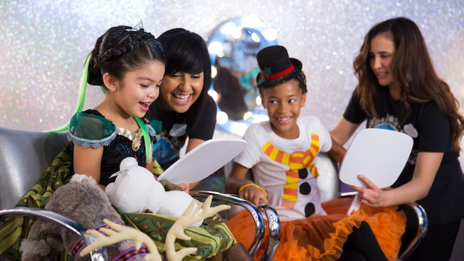 Young female Guests smile with Cast Members after being transformed into Anna and Olaf from 'Frozen'