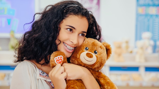 A teen girl hugs a Build A Bear