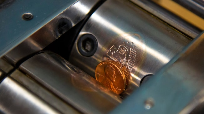Coin press machine with steel rollers engraving a Disneyland Diamond Celebration design onto a penny