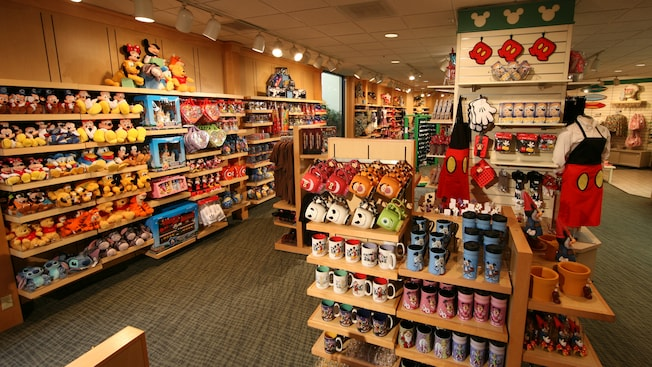 A shop with racks of Disney-themed merchandise, including mugs, stuffed animals, toys, apparel, kitchen supplies, pins, Mickey garden gnomes and pots