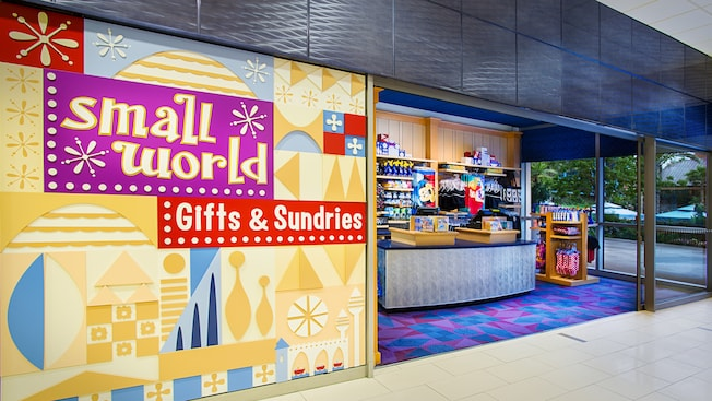 A simple shop with a sign that reads 'small world Gifts & Sundries' selling Disney-themed swimwear, sunscreen, towels, batteries, novelty electric fans and souvenirs