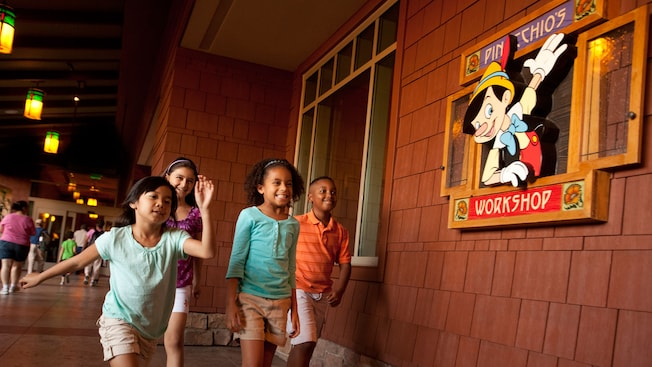 Four children skip outside Pinocchio's Workshop featuring a window-like sign with Pinocchio.
