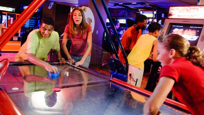 Teenage kids play air hockey at Starcade, a Tomorrowland attraction in Disneyland Park