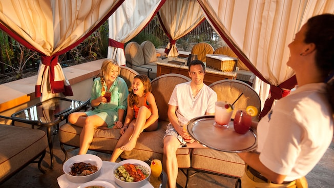 A waitress delivers drinks on a tray to a family of three sitting in a cabana