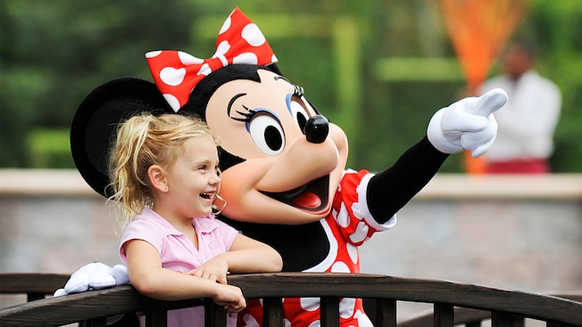 A laughing girl sits next to Minnie Mouse