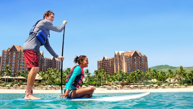 2 people ride a paddle board by a beach and 2 resorts
