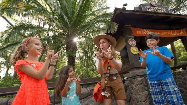 A Wilderness Explorer Troop Leader teaches children a special hand signal
