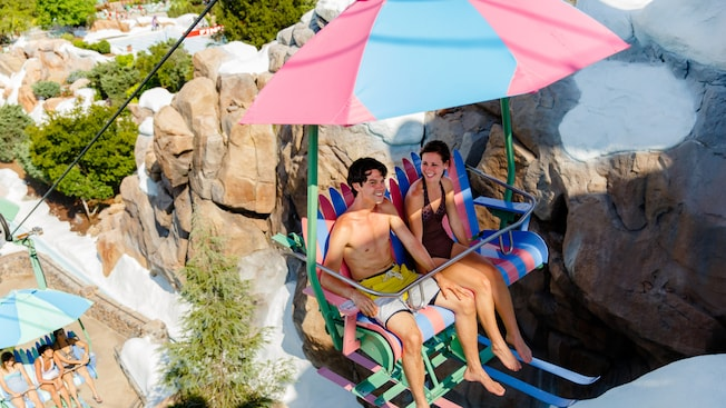 A teenaged boy and girl ride the colorful chairlift up Mount Gushmore at Disney's Blizzard Beach