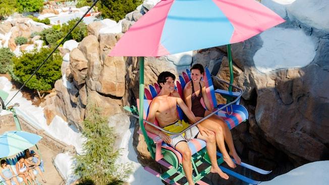 Dois adolescentes sobem em um teleférico colorido para o Mount Gushmore no Disney's Blizzard Beach