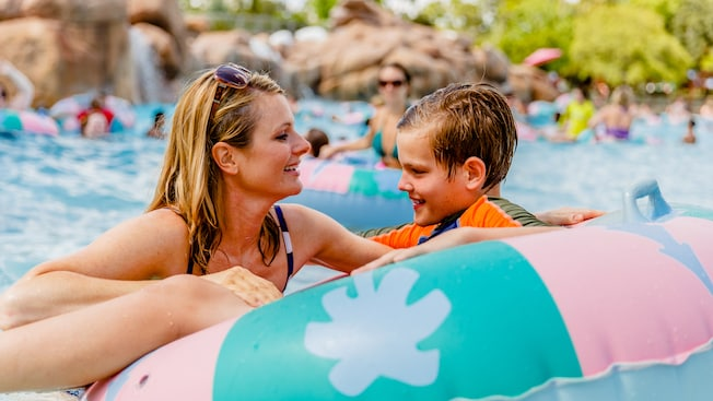 A mother plays with her son who's sitting in an inner tube in Melt-Away Bay