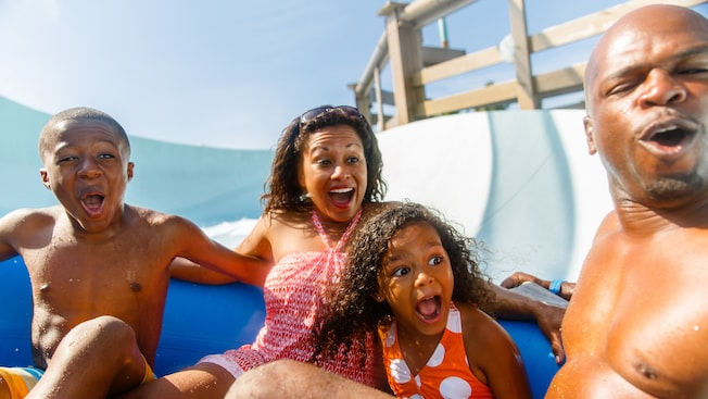 A family of 4 share a raft at Teamboat Springs, a whitewater attraction at Disney's Blizzard Beach