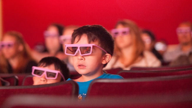 Two young children wear 3D glasses and watch a movie