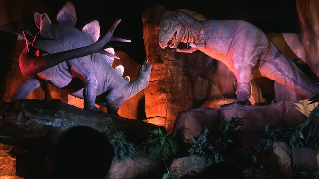 A tyrannosaurus rex and stegosaurus face off in a darkened, prehistoric cave