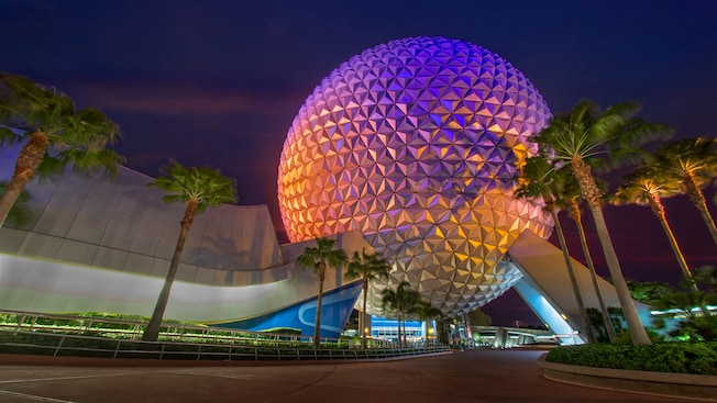 Evening lights casting a colorful glow onto Spaceship Earth as it rises into the sky above Epcot