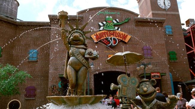 Une statue de Miss Piggy habillée en statue de la Liberté et une statue de l'ours Fozzie tenant un appareil photo