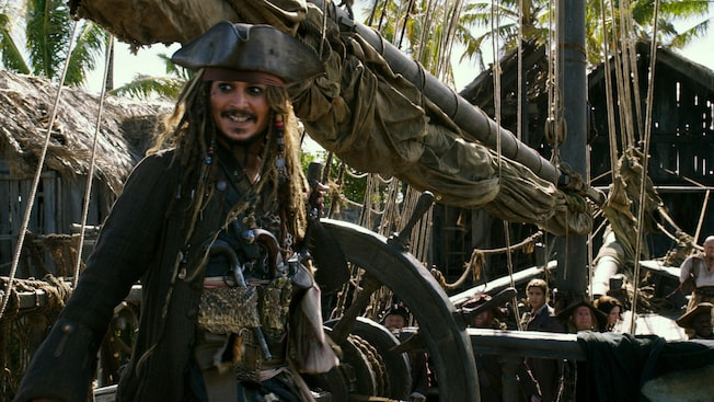 Captain Jack Sparrow sorri a bordo do navio conhecido como The Black Pearl, repleto de piratas