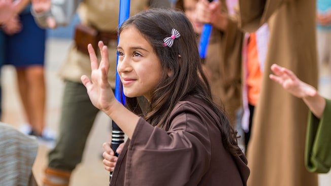 Uma menina usando vestes Jedi segura um sabre de luz de brinquedo com a mão direita e ergue a mão esquerda