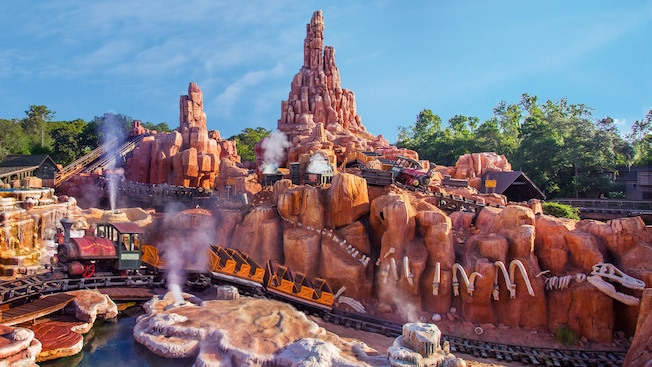 Mining trains zoom over rugged terrain on Big Thunder Mountain Railroad in Frontierland