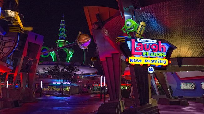 Una estatua de Mike Wazowski ubicada sobre un letrero de Monsters, Inc. Laugh Floor en Tomorrowland por la noche