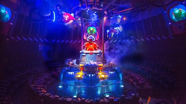 Stitch emerge de un tubo de transporte en un teatro circular